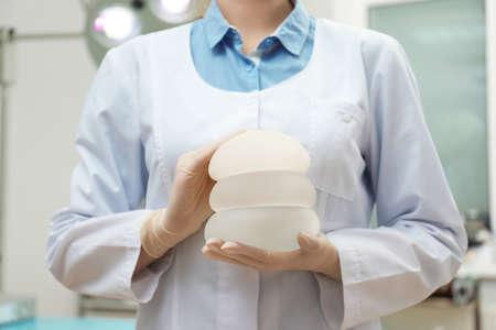 Foto de Doctor holding silicone implants for breast augmentation in clinic, closeup. Cosmetic surgery - Imagen libre de derechos