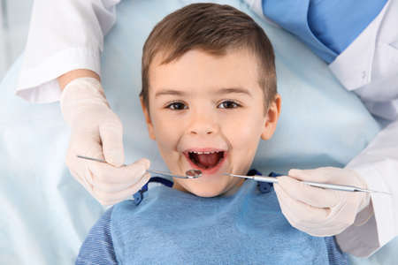 Photo pour Dentist examining cute boy's teeth in modern clinic - image libre de droit