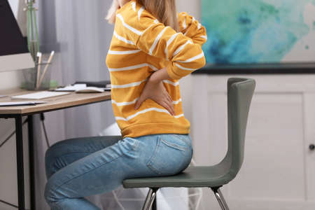 Photo pour Young woman suffering from back pain in office, closeup - image libre de droit