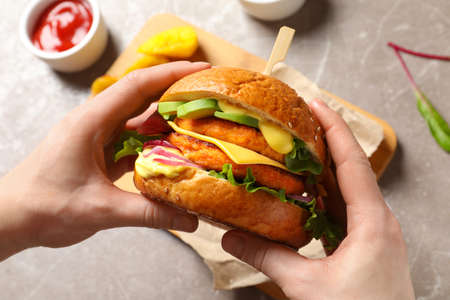Foto per Woman holding tasty vegetarian burger over table, top view - Immagine Royalty Free