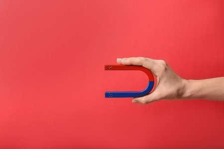 Foto de Woman holding magnet on color background, closeup. Space for text - Imagen libre de derechos