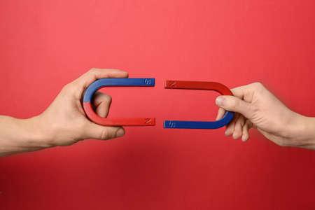 Foto de People holding magnets on color background, closeup - Imagen libre de derechos