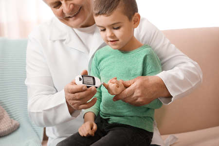 Foto per Doctor measuring patient's blood sugar level with digital glucose meter at home. Diabetes control - Immagine Royalty Free