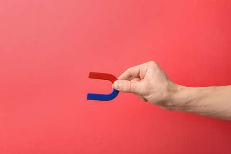 Foto de Man holding magnet on color background, closeup. Space for text - Imagen libre de derechos