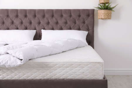 Foto de Comfortable bed with new mattress in room. Healthy sleep - Imagen libre de derechos