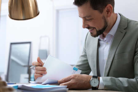 Photo pour Businessman working with documents at table in office - image libre de droit