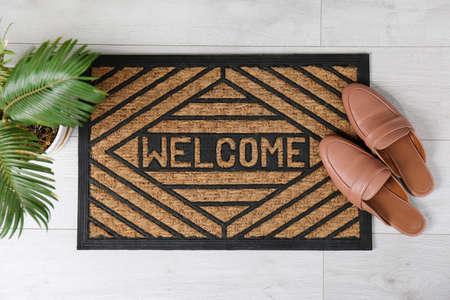 Foto de Door mat with word WELCOME and shoes on floor, top view - Imagen libre de derechos