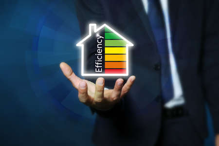 Foto de Businessman holding house icon with energy efficiency rating against color background, closeup - Imagen libre de derechos