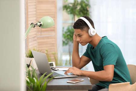 Foto de African-American teenage boy with headphones using laptop at table in room - Imagen libre de derechos