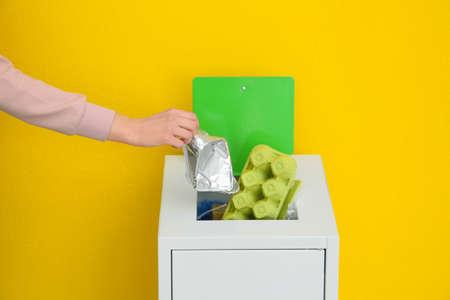 Foto de Woman putting used foil container into trash bin on color background, closeup. Recycling concept - Imagen libre de derechos