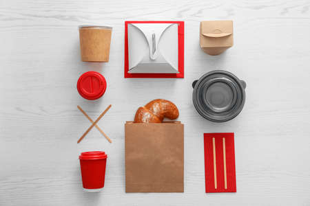 Photo pour Flat lay composition with paper bag and different takeaway items on wooden background. Space for design - image libre de droit