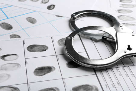Foto per Handcuffs and fingerprint record sheets, closeup. Criminal investigation - Immagine Royalty Free