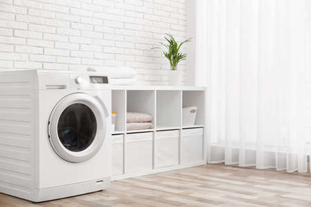 Foto per Modern washing machine near brick wall in laundry room interior, space for text - Immagine Royalty Free