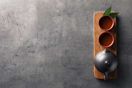Foto de Board with cups and teapot of freshly brewed oolong on grey background, top view with space for text - Imagen libre de derechos