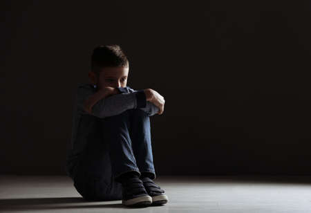 Photo for Upset boy sitting in dark room. Space for text - Royalty Free Image