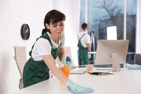 Photo pour Professional janitor cleaning table in modern office - image libre de droit