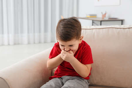 Photo pour Little boy suffering from nausea in living room - image libre de droit