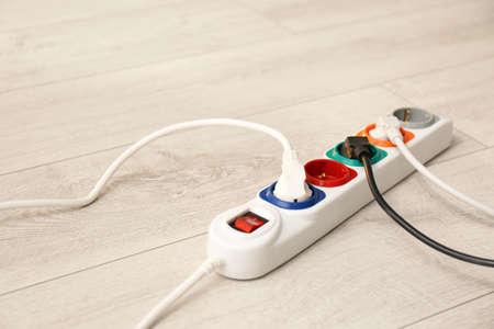 Photo pour Extension cord on floor, space for text. Electrician's professional equipment - image libre de droit