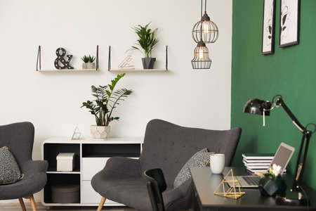 Photo pour Modern living room interior with workplace near green wall - image libre de droit