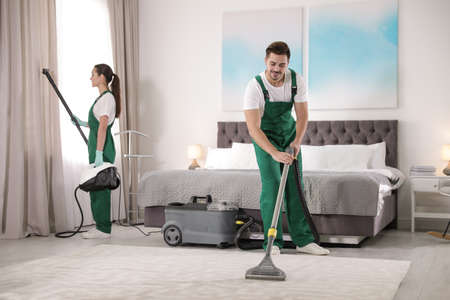 Foto de Team of janitors cleaning bedroom with professional equipment - Imagen libre de derechos