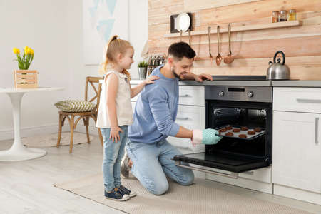 Photo pour Father with his daughter baking cookies in oven at home - image libre de droit