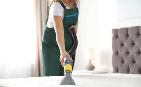 Foto de Janitor cleaning mattress with professional equipment in bedroom, closeup - Imagen libre de derechos