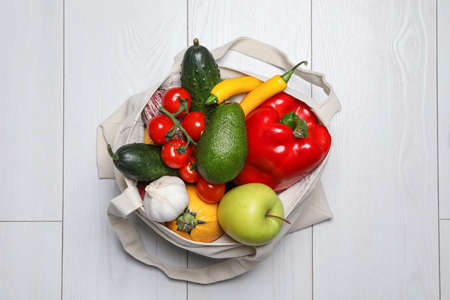Photo for Bag full of fresh vegetables and fruits on light background, top view - Royalty Free Image