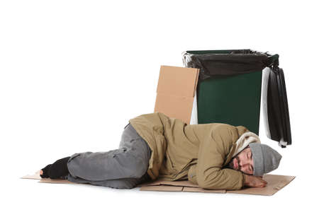 Foto de Poor homeless man lying near trash bin isolated on white background - Imagen libre de derechos