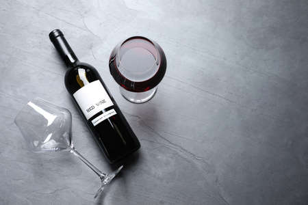 Foto de Glasses and bottle with red wine on color background, flat lay. Space for text - Imagen libre de derechos
