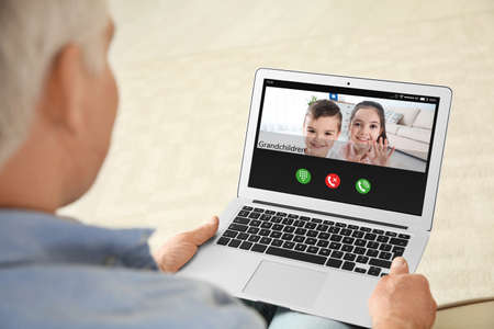 Foto de Closeup view of senior man talking with grandchildren via video chat at home - Imagen libre de derechos