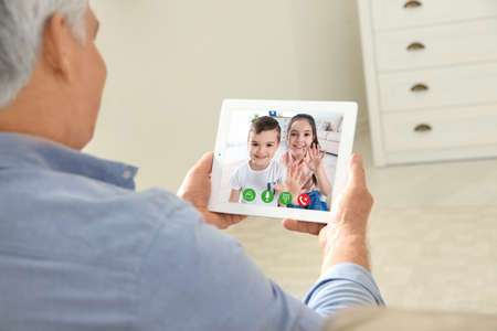 Photo pour Closeup view of senior man talking with grandchildren via video chat at home - image libre de droit