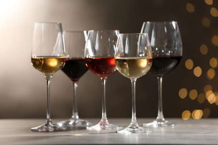 Photo pour Glasses with different wines on grey table against defocused lights - image libre de droit
