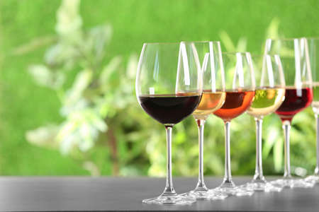 Foto de Row of glasses with different wines on grey table against blurred background. Space for text - Imagen libre de derechos