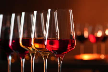 Foto de Row of glasses with different wines against blurred background, closeup. Space for text - Imagen libre de derechos