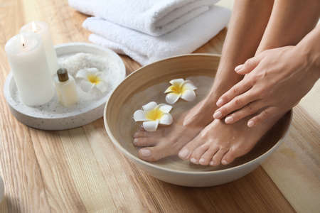 Foto de Closeup view of woman soaking her feet in dish with water and flowers on wooden floor. Spa treatment - Imagen libre de derechos