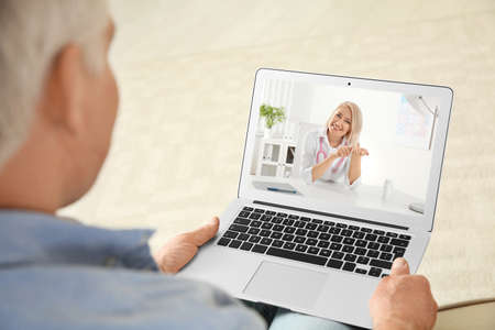 Photo for Man using laptop for online consultation with doctor via video chat at home, closeup - Royalty Free Image