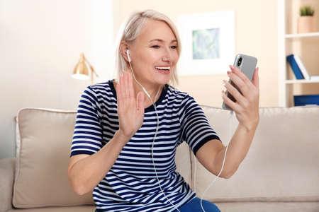 Photo pour Mature woman using video chat on mobile phone at home - image libre de droit