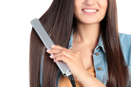 Photo pour Young woman using hair iron on white background, closeup - image libre de droit