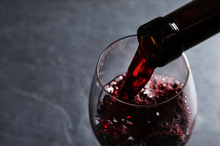 Photo pour Pouring red wine from bottle into glass on grey background, closeup. Space for text - image libre de droit