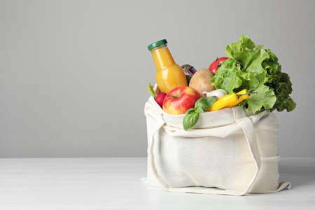 Foto de Cloth bag with vegetables and bottle of juice on table against grey background. Space for text - Imagen libre de derechos
