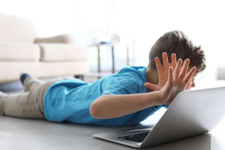 Photo pour Frightened little child with laptop on floor indoors. Danger of internet - image libre de droit