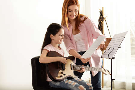 Photo for Little girl playing guitar with her teacher at music lesson. Learning notes - Royalty Free Image