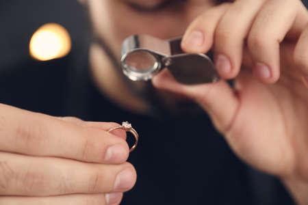 Photo pour Male jeweler evaluating ring in workshop, closeup - image libre de droit