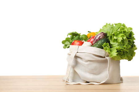 Photo pour Cloth bag with vegetables on table against white background. Space for text - image libre de droit