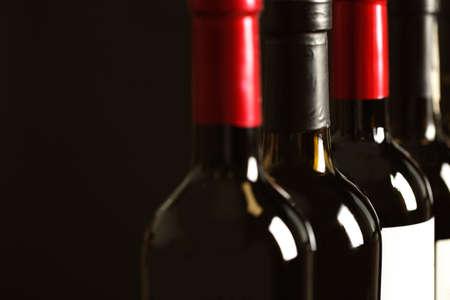 Foto de Bottles of different wines on dark background, closeup. Expensive collection - Imagen libre de derechos