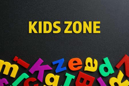 Photo pour Phrase KIDS ZONE made of plastic magnetic letters on black background, top view - image libre de droit