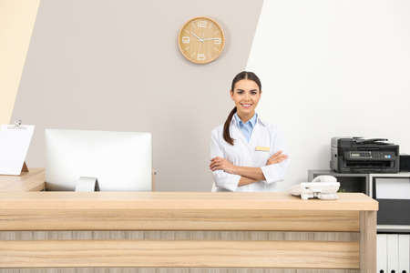 Photo pour Portrait of receptionist at desk in modern clinic - image libre de droit