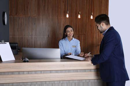 Photo pour Receptionist registering client at desk in lobby - image libre de droit