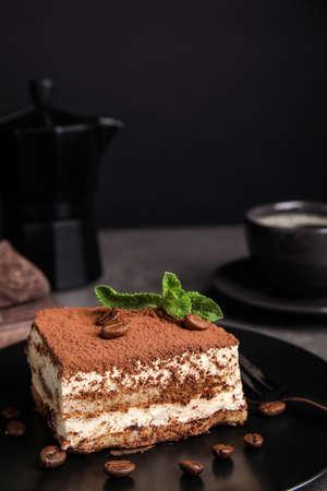 Photo pour Composition with tiramisu cake on table against dark background - image libre de droit