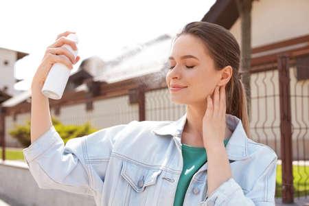 Foto de Young woman applying thermal water on face outdoors. Cosmetic product - Imagen libre de derechos